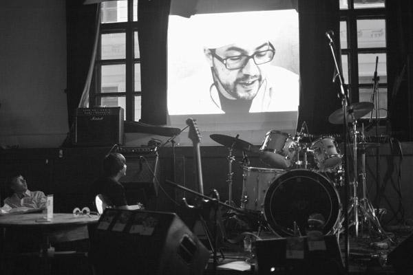 На фото: Чой, Миша (в зале), доктор Коган (на экране); просмотр «клипа о клипе». Презентация клипа на песню «Здравствуй» в клубе «Мастерская».