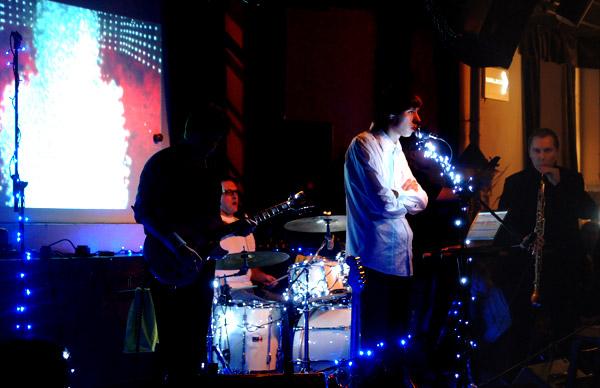 Мишин силуэт, Лёня, Чой, Юра (почти невидимый) и Денис Голубев. Презентация альбома «Без мая», звучит песня «И-и-и-и».