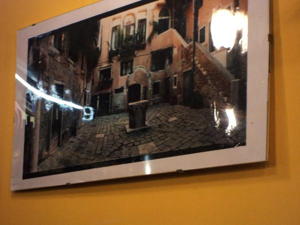 Блик девять на фотографии венецианского двора, висящей в венецианской остерии. Венеция, Италия.
