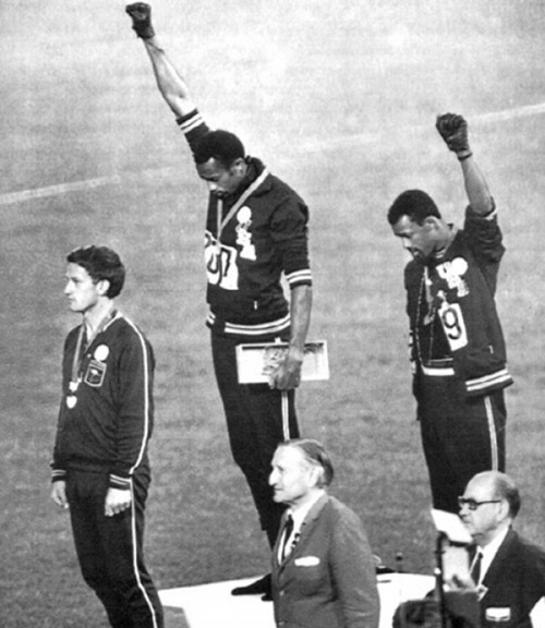 На летних Олимпийских Играх 1968 года в Мехико призеры Джон Карлос и Томми Смит во время исполнения национального гимна подняли кулаки как символ лозунга «Власть черным» и в знак протеста от имени «Олимпийского проекта за права человека». Фотограф: AP photographer.